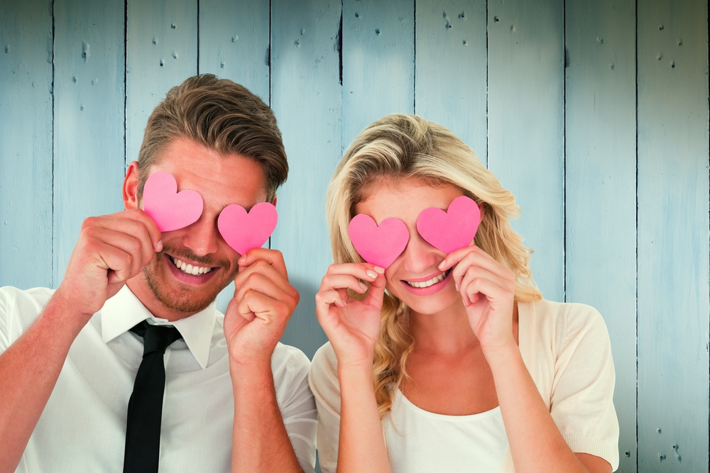 Attractive young couple holding pink hearts over eyes against wooden planks.jpeg